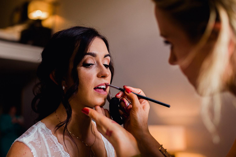 makeup artist putting lipstick on a bride