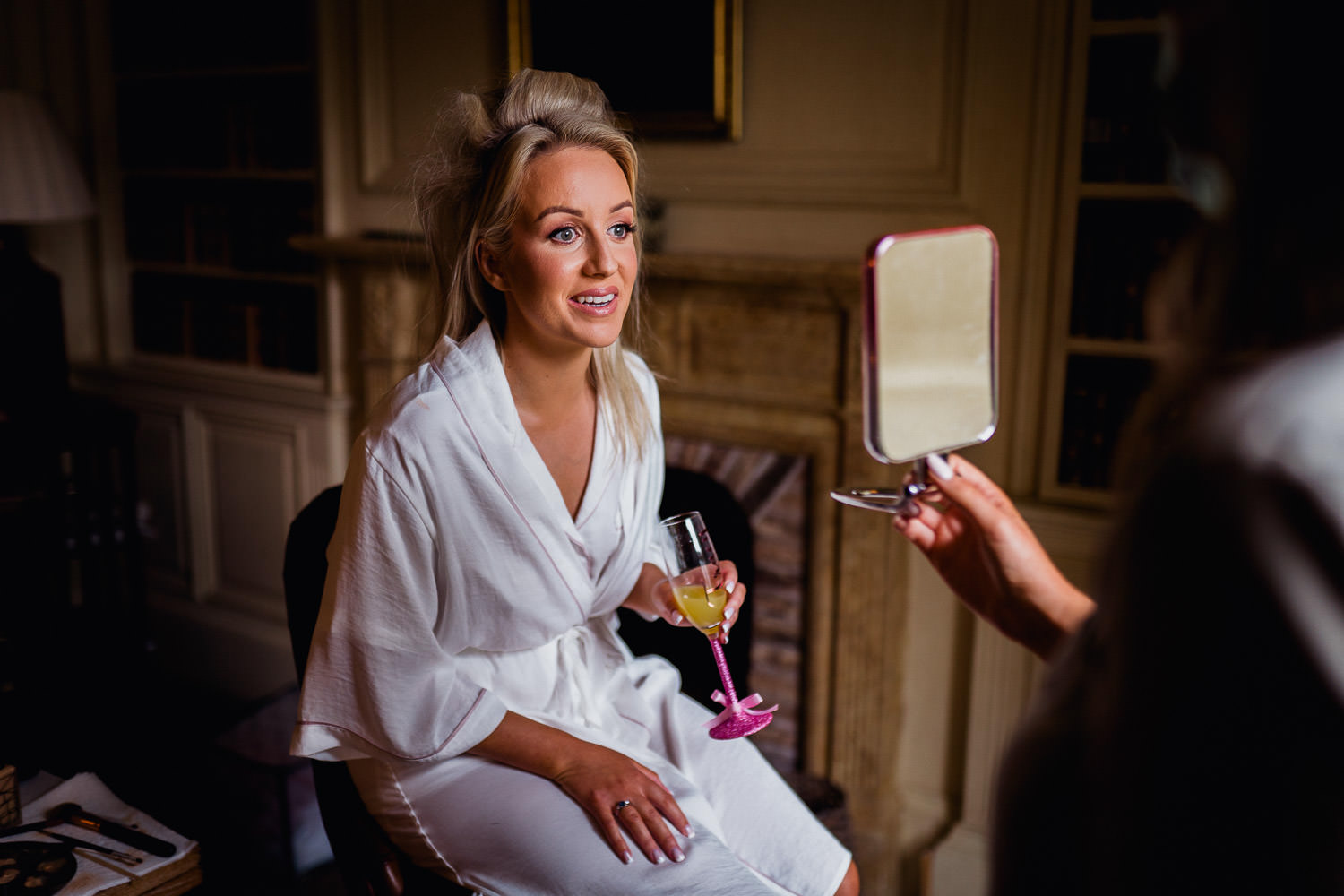 bride looking in the mirror after having her makeup done