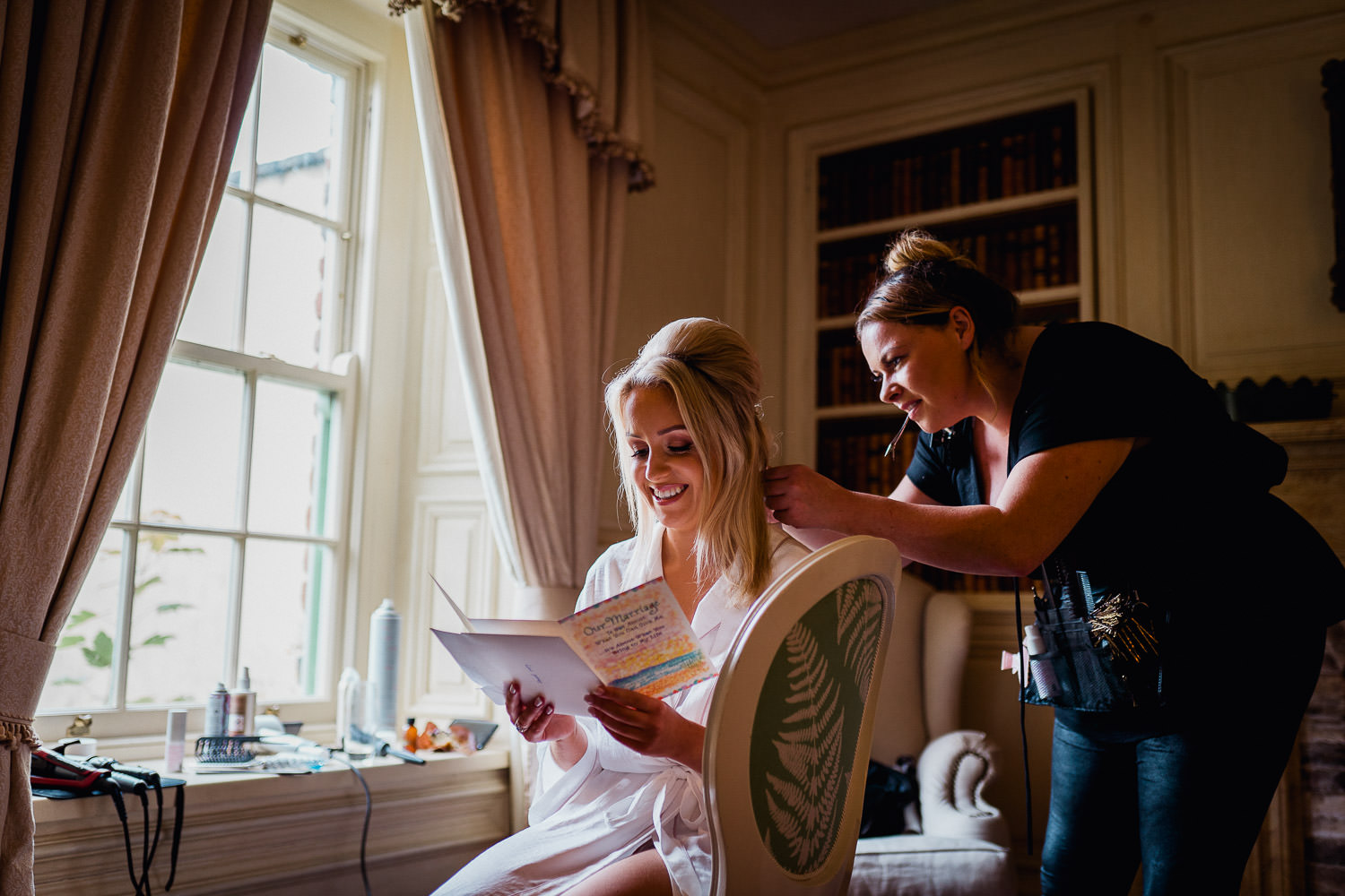 bride reading a wedding card while having her hair done