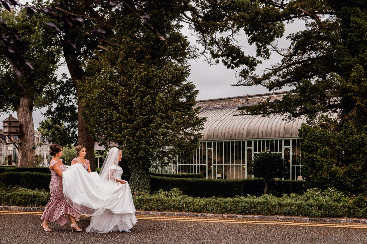 bridesmaids carrying the brides dress at Cliff at Lyons