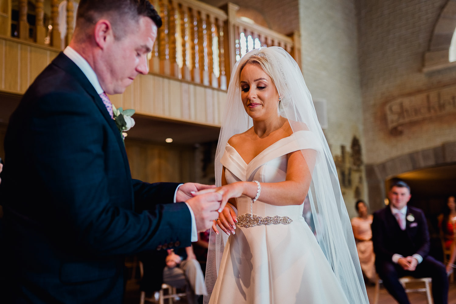groom putting a ring on the bride finger