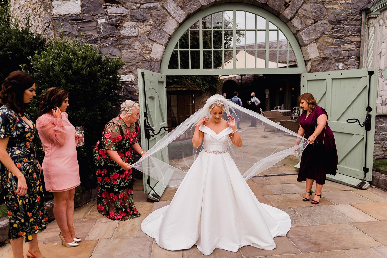 wedding guests fixing brides veil