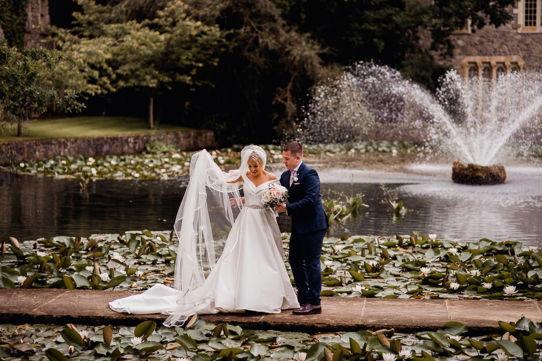 groom fixing brides dress at Cliff at Lyons