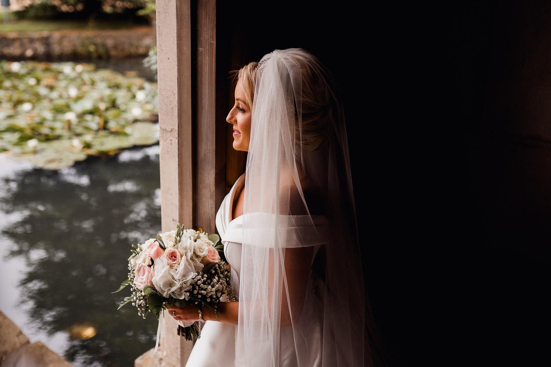 bride standing in doorway holding flowers