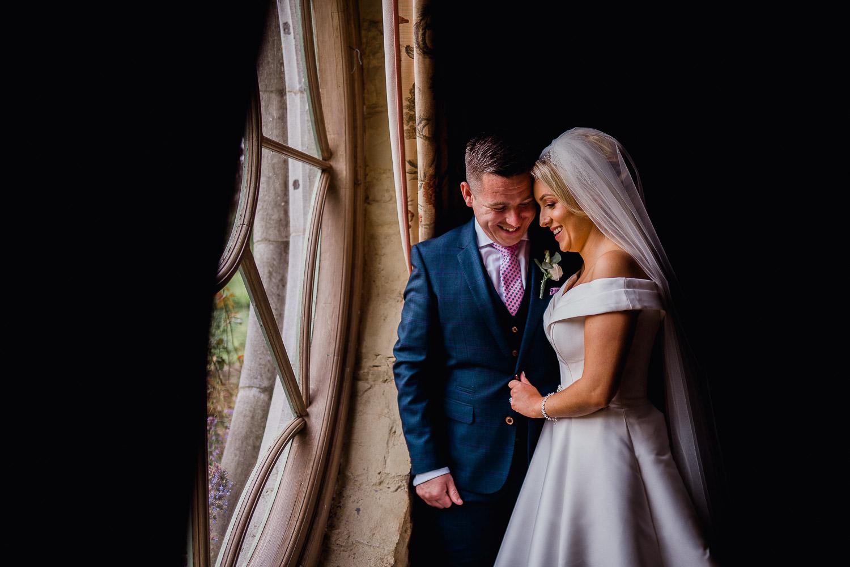 bride and groom standing in window light