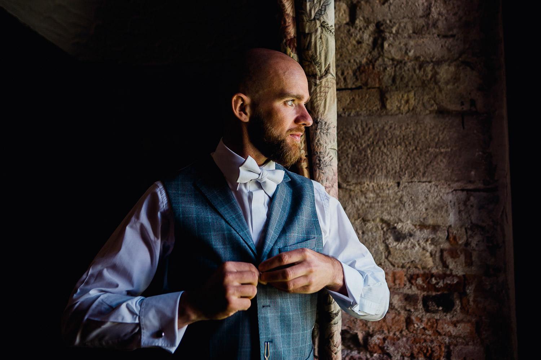groom closing his waist coat at Kinnitty Castle