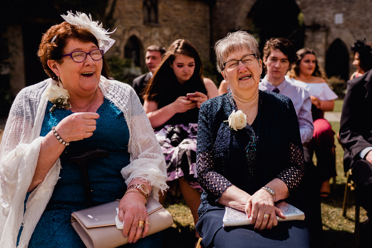 two women laughing during  a wedding ceremony