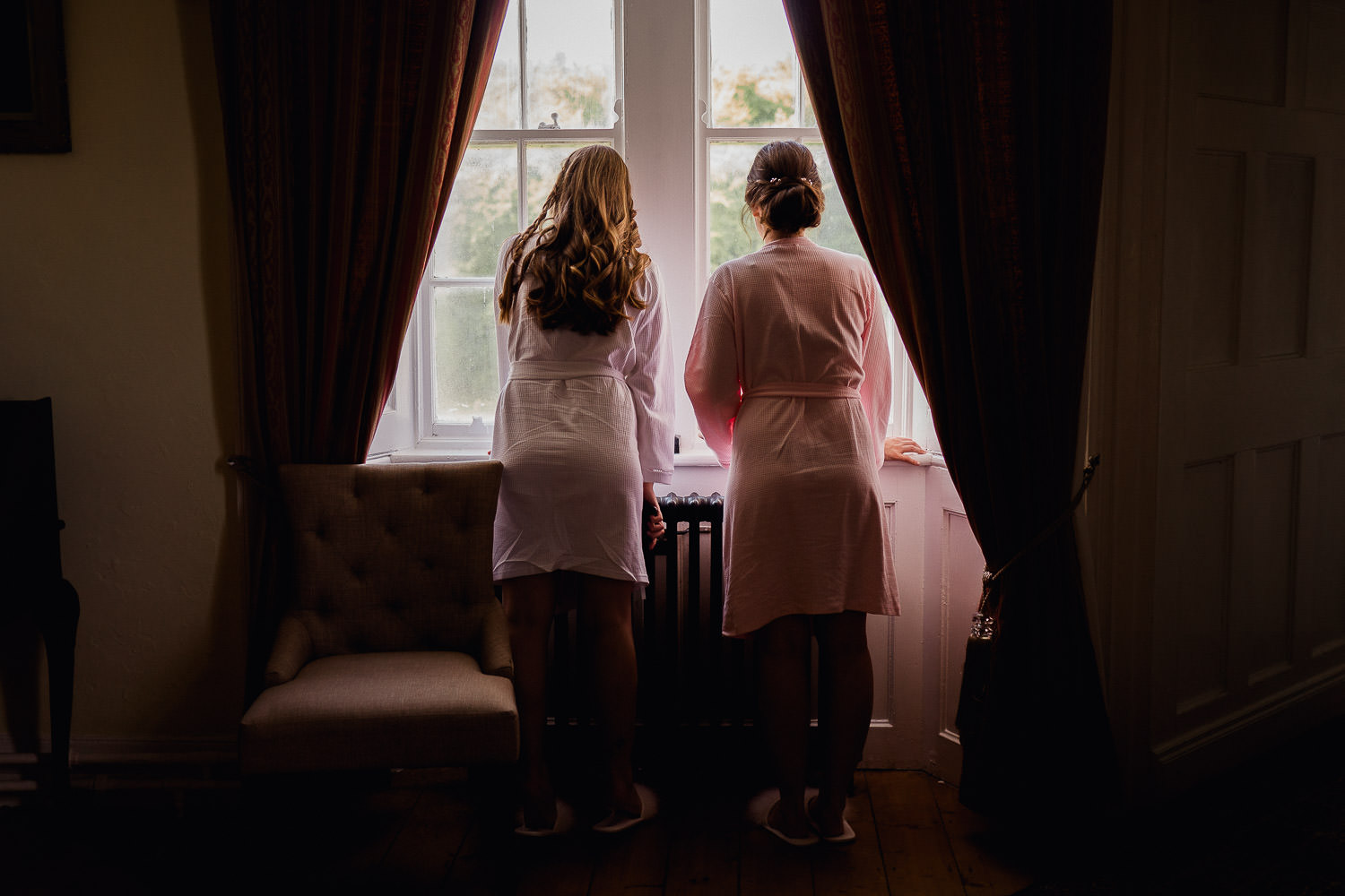 Bride and bridesmaid looking out a window