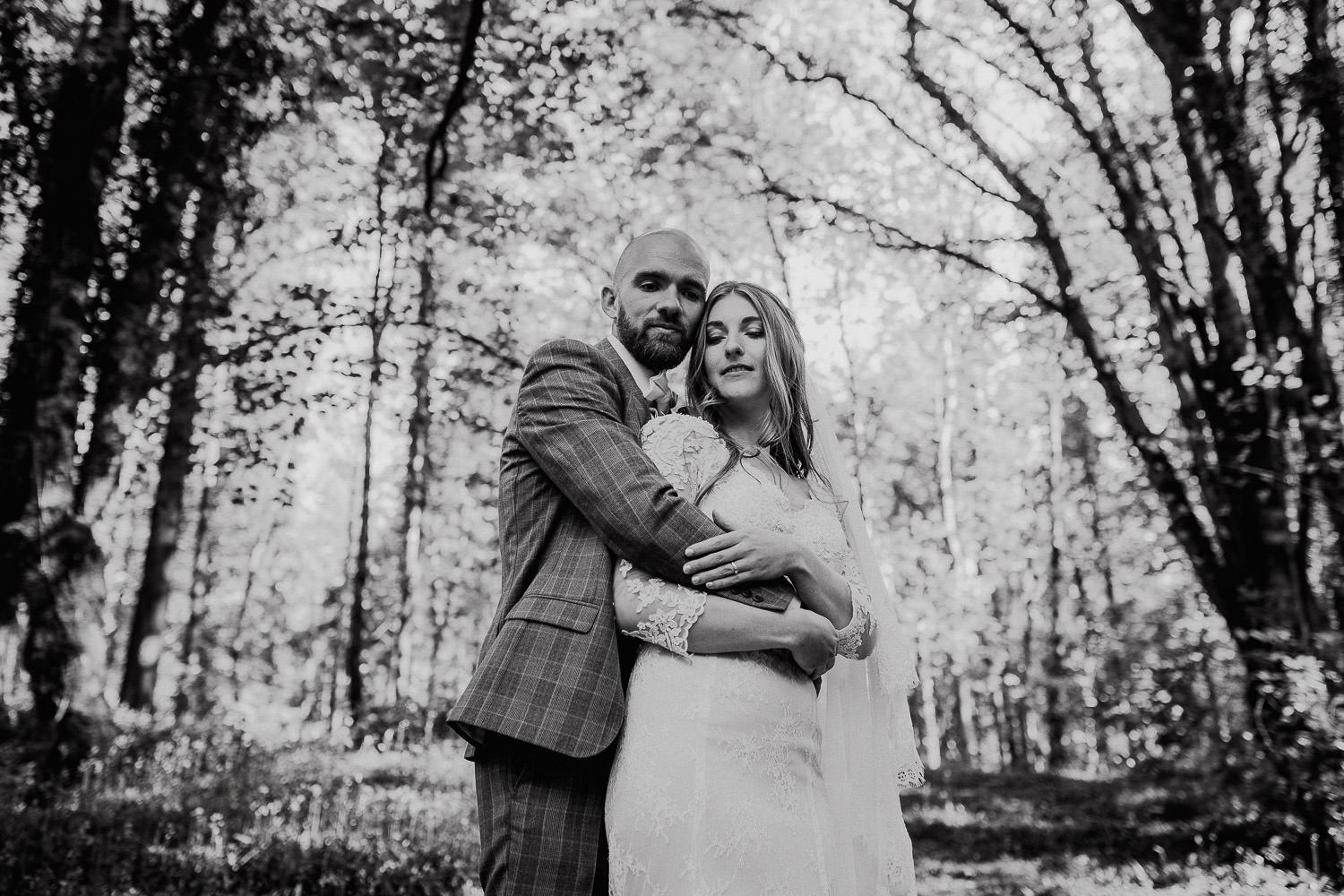 Bride and groom hugging in a forest