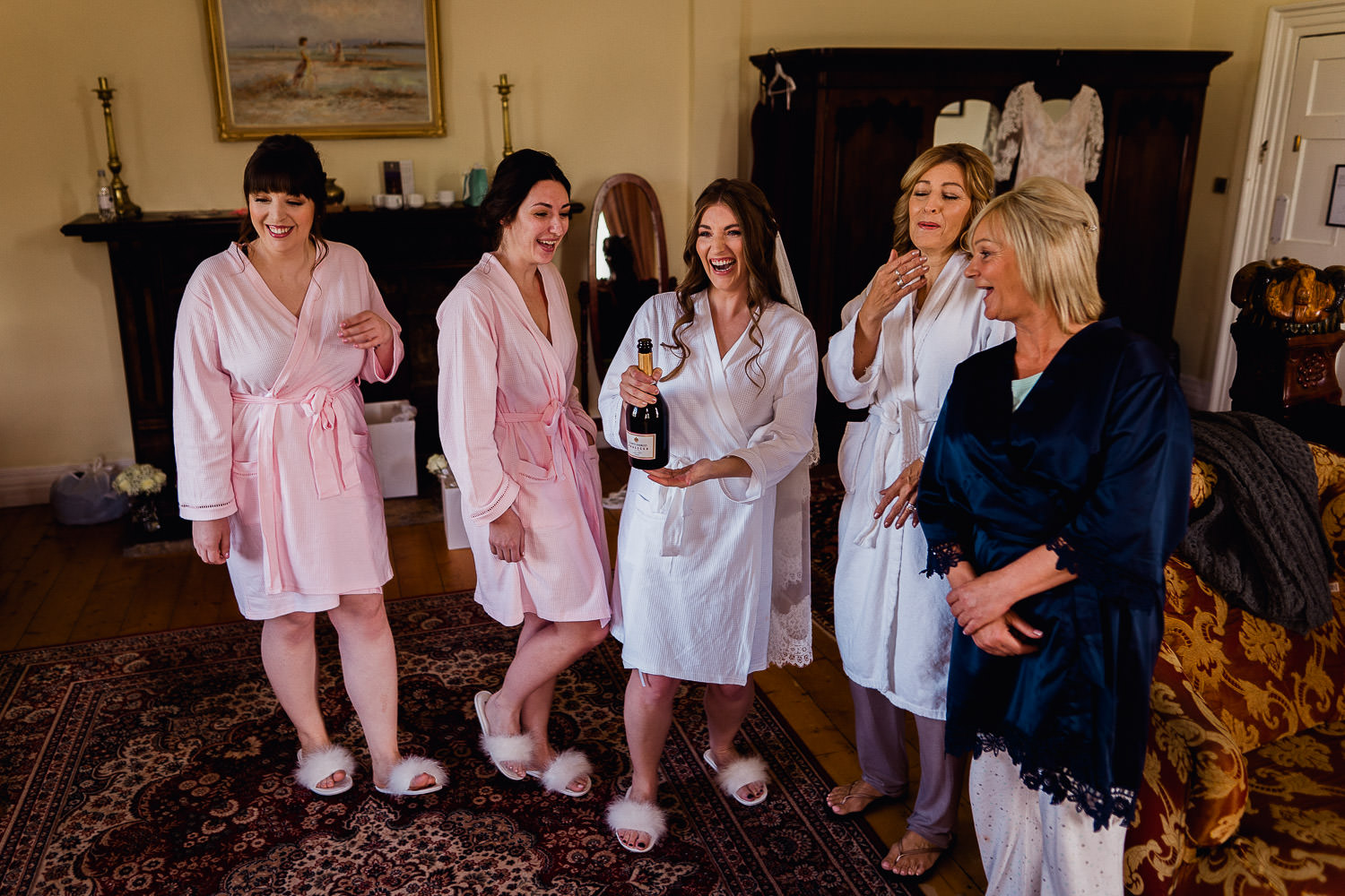 Bridal party opening a bottle champagne
