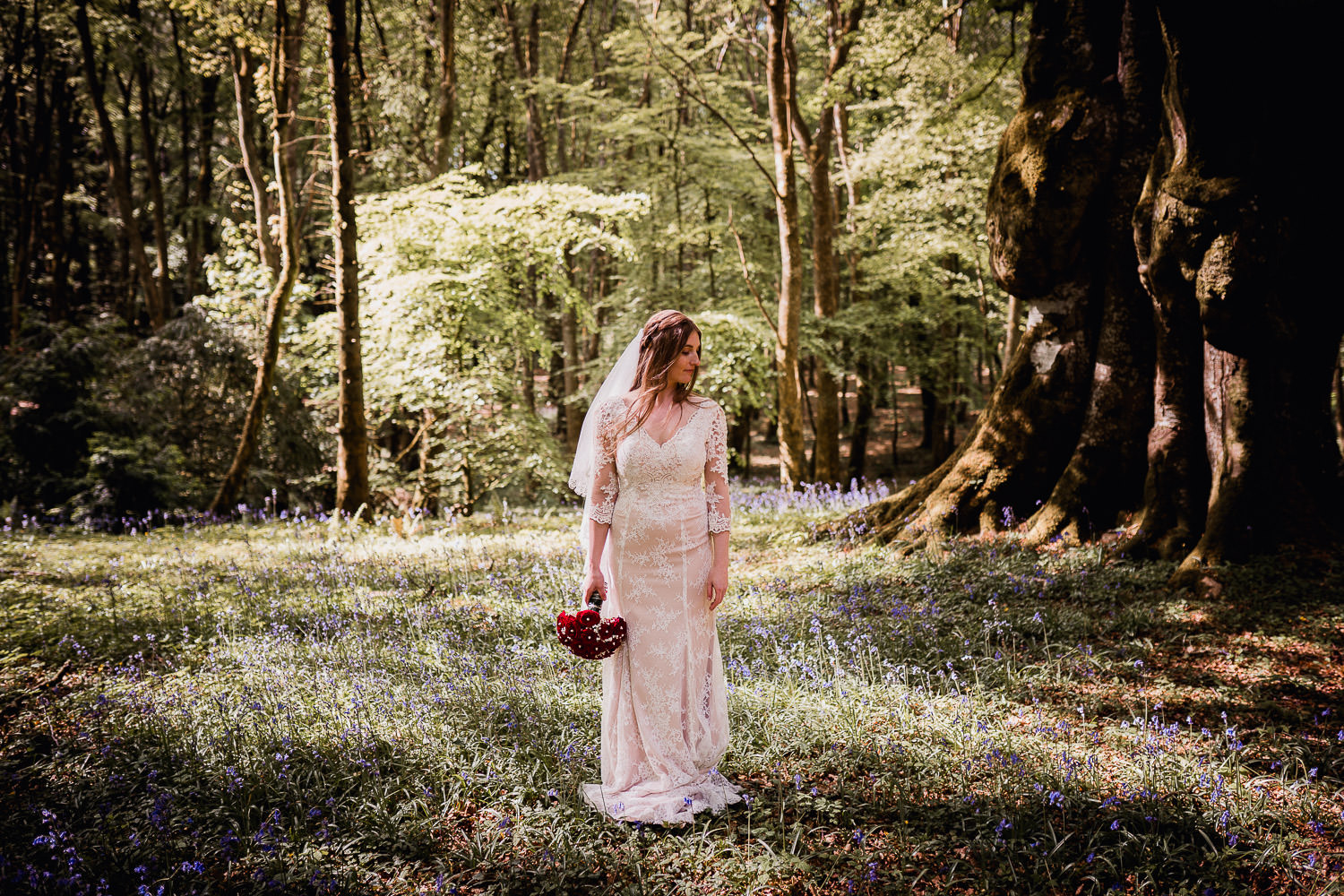 bride standing in a bluebell forest