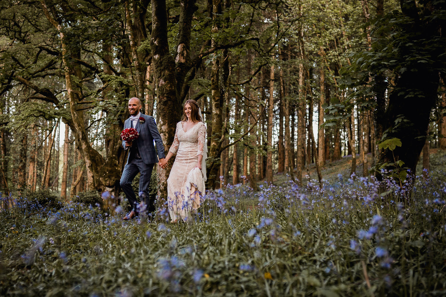 bride and groom walking in a bluebell forest