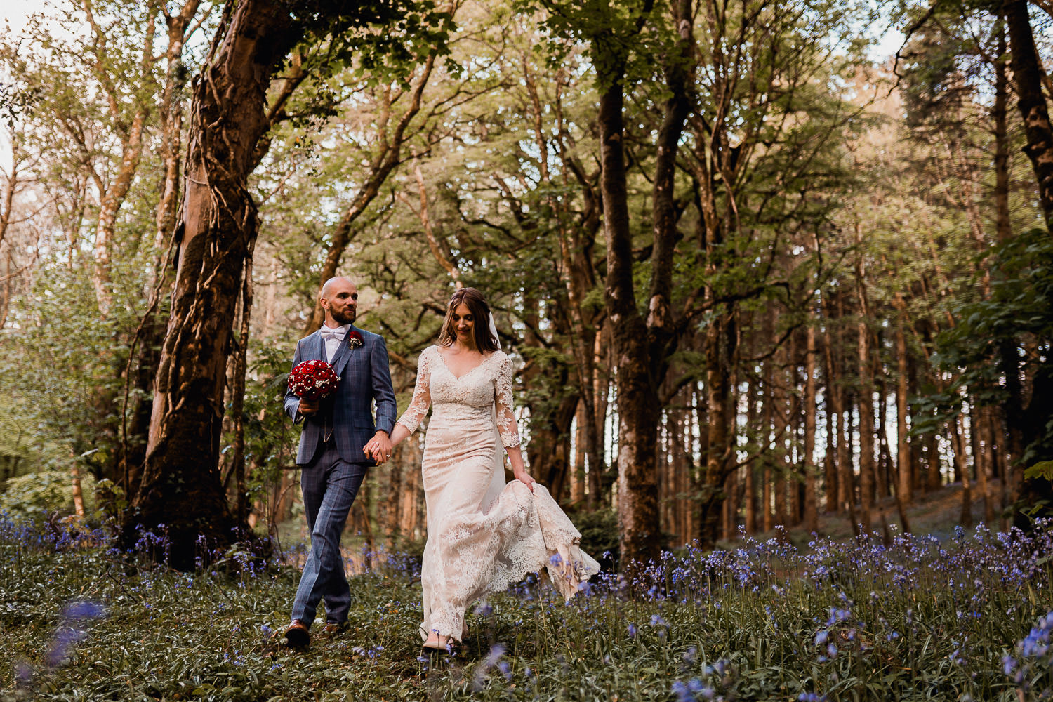 bride and groom standing in a bluebell forest